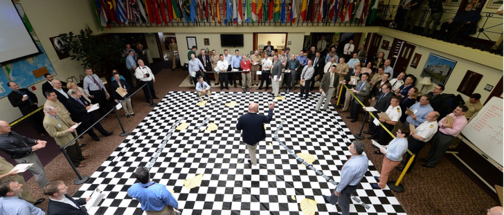 A bald white man in a black jacket and khaki pants stands in the middle of a black and white checkered floor. He is speaking to a room of white men and women, who are all dressed in business clothing. In the background is a row of flags of the world.