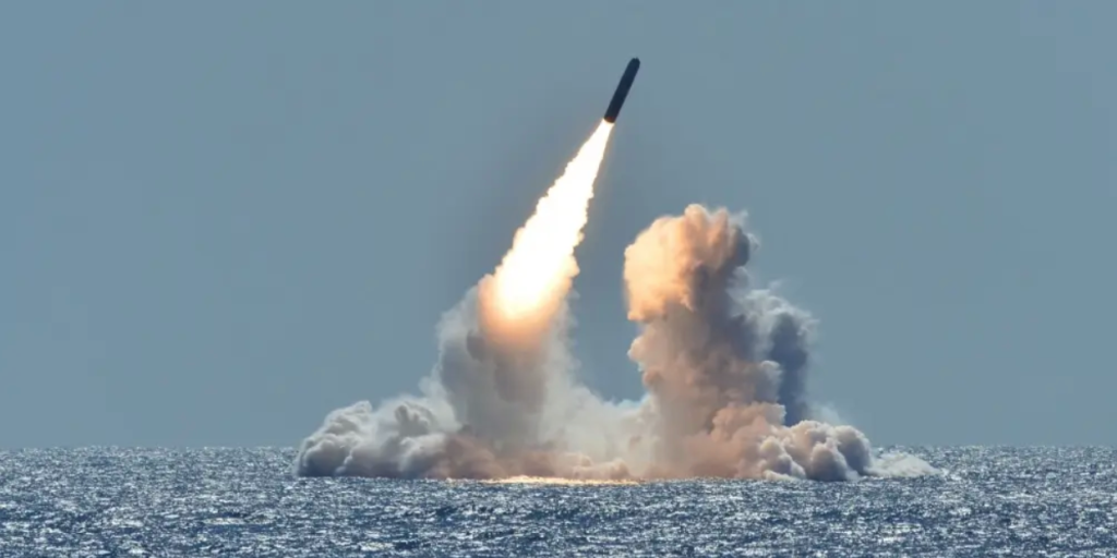 A grey, cylindrical rocket launches into the air with a jet of fire behind it and two pillars of smoke. The rocket is at an angle and appears to be moving upwards away from the ocean.